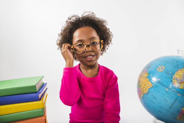 Girl with glasses next to school supplies