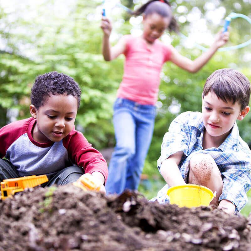 Preschoolers digging in dirt